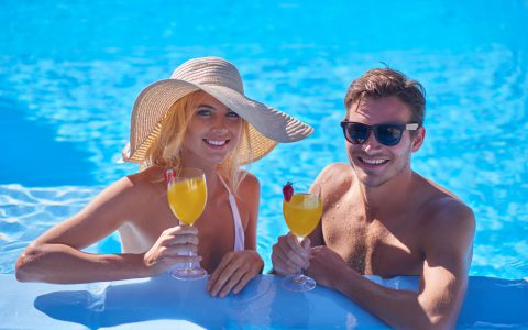 Couple in pool with cocktails.