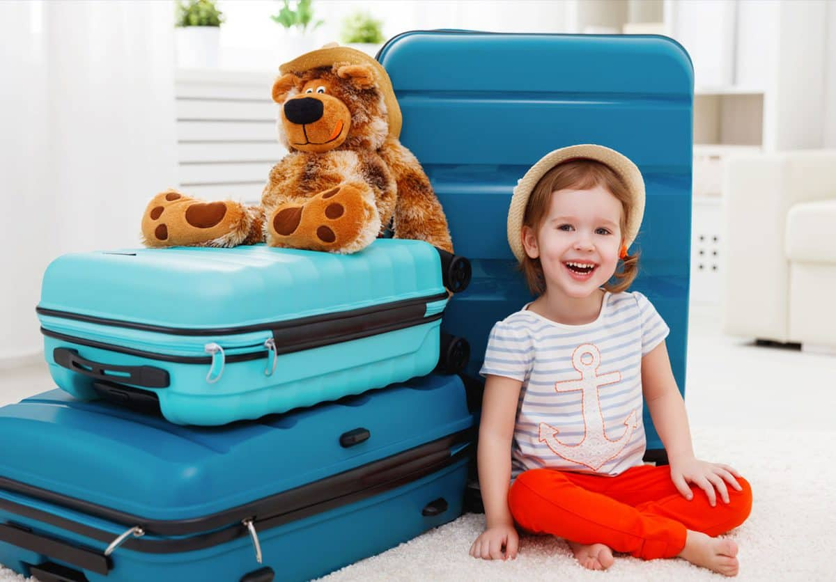 child next to luggage