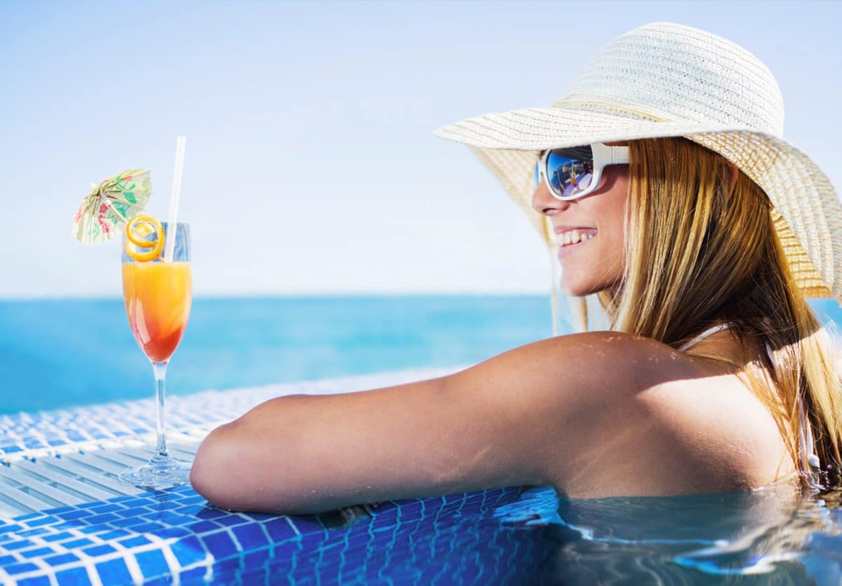 single lady with cocktail in pool