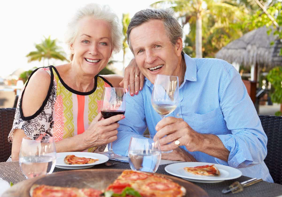 Smiling Retired Couple Eating at Resort